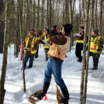 Students in yellow jackets standing in snow amongst trees