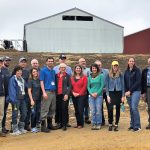Large group photo of men and women smiling and facing the camera. Outside, near a barn