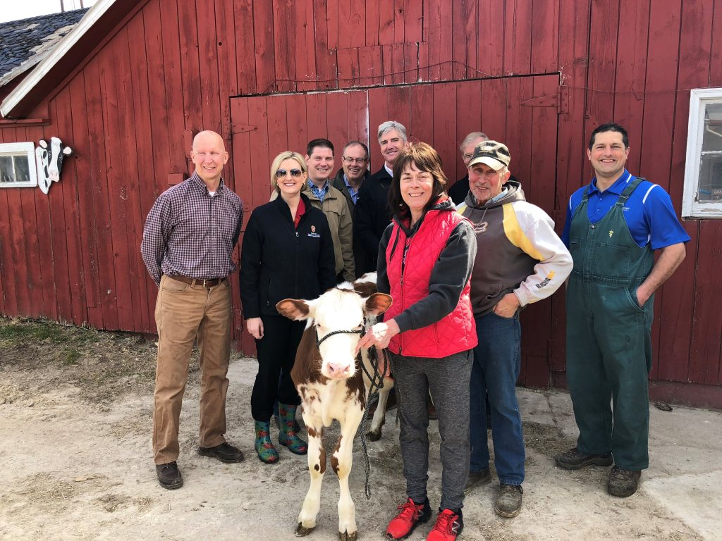 Small calf is being held by a woman and other adults posing and smiing for camera in front of a redbarn